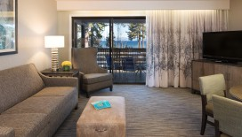 Enjoy time together in the Living Room of the Deluxe Two Bedroom Suite, featuring a Flat Screen television and access to the balcony with views of Lake Tahoe.